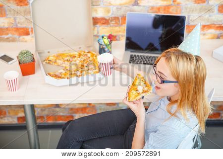 Smiling office lady, at lunchtime and eating pizza. Festive atmosphere. A girl in a festive cap on her head.