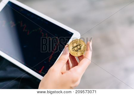 a tablet in the hands of a girl. The girl is holding a gold coin in her hands, a plan of a skull. Crypto currency, bitcoins.