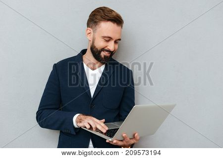 Full length image of smiling bearded man in business clothes using laptop computer over gray background
