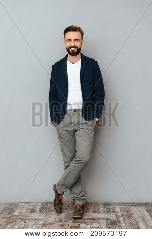 Full length image of smiling bearded man in business clothes holding arms in pocket and looking at the camera over gray background