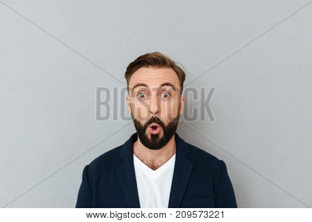 Shocked bearded man in business clothes looking at the camera over gray background