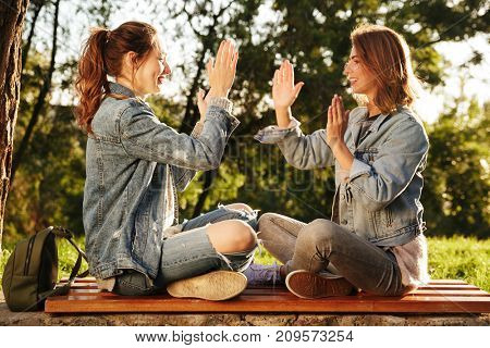 Two attractive young girls in casual jeans wear clap their hands while sitting on wooden bench in park outdoor