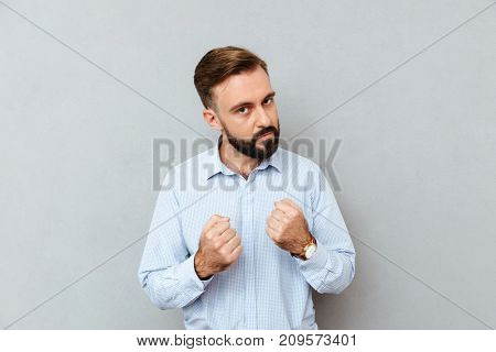 Serious bearded man in business clothes ready to fight and looking at the camera over gray background