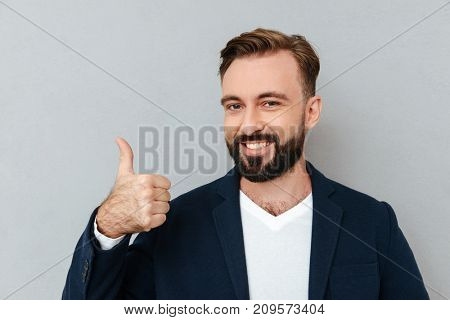 Cheerful bearded man in business clothes showing thumb up and looking at the camera over gray background