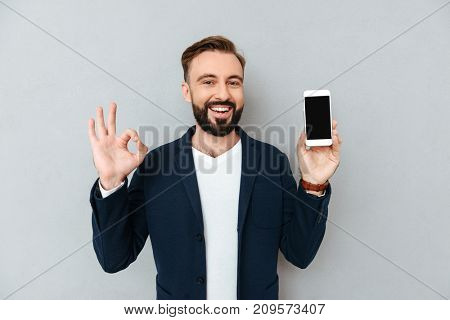 Happy bearded man in business clothes showing blank smartphone screen while showing ok sign and looking at the camera over gray background
