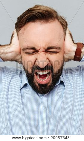 Vertical image of screaming bearded man in business clothes covering his ears over gray background