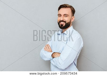 Pleased bearded man in business clothes with crossed arms looking at the camera over gray background