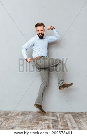 Full length image of screaming bearded man in business clothes rejoice and jumping over gray background