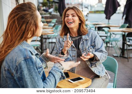 Two young cheerful female friends talking while sitting in cite cafe