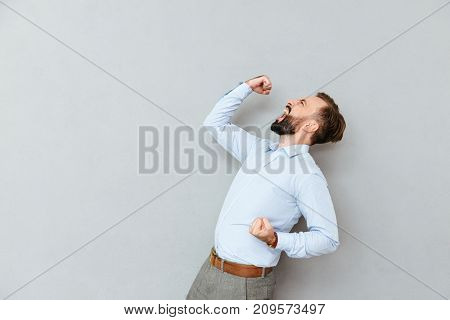 Side view of Screaming happy bearded man in business clothes rejoice over gray background