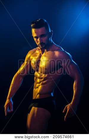Athlete performs at competitions in black shorts with naked bare body against blue background. Man bodybuilder. Athletic man with biceps shoulders triceps chest abs six pack. Male model sexy