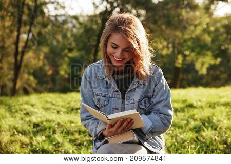Cheerful young woman in jeans jacket reading a book in sunny park