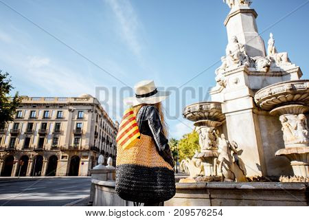 Young woman tourist with catalan flag standing in front of the fountain in Barcelona city