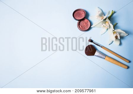 Powder, brush and flower on a blue background