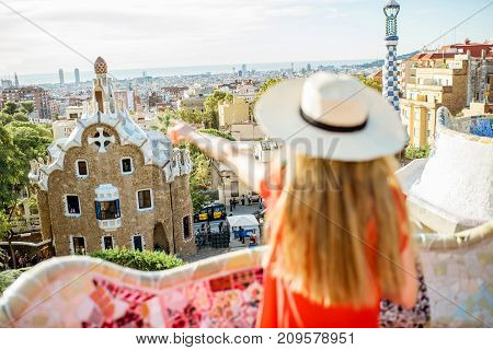 Young woman tourist in red dress enjoying great view on Barcelona city in famous Guell park. Image focused on the background