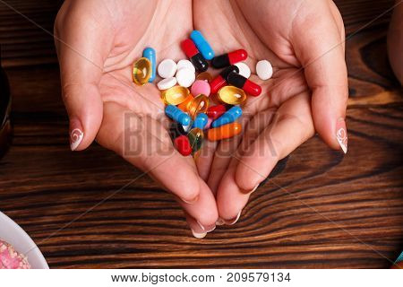 Female holding different tablets in her hands. Panacea, life save service, prescribe medication, legal drug store, disease healing, blood pressure concept