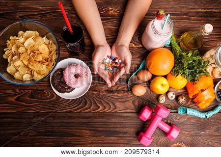Healthy lifestyle or fast food and drugs. Fast Food with chips, donuts, soda and tablets in hands vs healthy lifestyle with sport, diet, fresh fruits and dumbbells