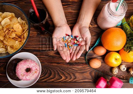 Healthy lifestyle or fast food and drugs. Fast Food with chips, donuts, soda and tablets in hands vs healthy lifestyle with sport, diet, fresh oranges, apples, smoothies and dumbbells