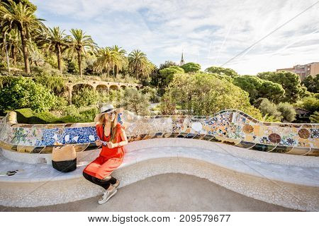 Young woman tourist in red dress sitting on the bench decorated with mosaic in the famous Guell park in Barcelona. Wide angle image with copy space