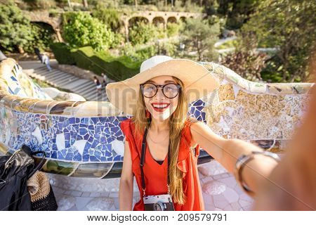 Young woman tourist in red dress making selfie photo sitting on the bench decorated with mosaic in the famous Guell park in Barcelona