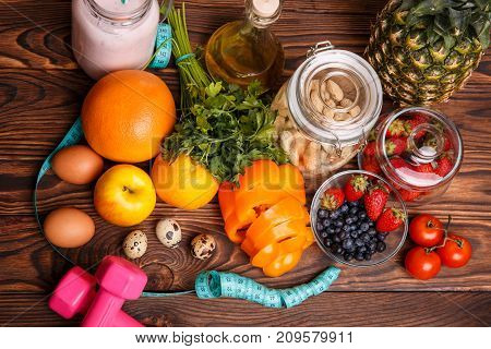 The concept of dietary fitness nutrition with pineapple, orange, grapefruit, apple, sweet pepper, measuring tape, eggs, greens, blueberries, strawberries, tomatoes and rampant eggs