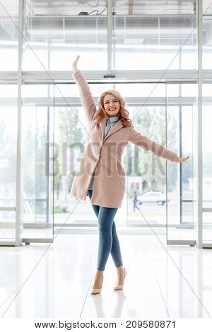 Beautiful blonde young girl in a beautiful beige coat, jeans and high heels. Comes to the mall. Happy woman raised her arms to the top on the background of glass doors. In full growth.