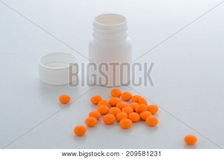 Orange Tablets Spilled Out Of The Plastic Bottle And Lie Next To