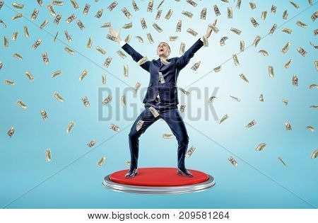 A happy and victorious businessman stands on a giant red button under many falling 100 dollar bills. Lottery winner. Business and profit. Easy money.