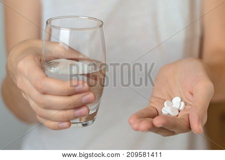 Female Hands Hold Pills And A Glass Of Water