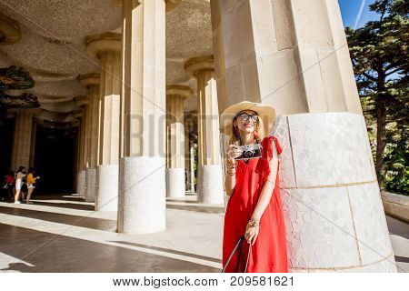 Happy woman tourist in red dress with hat and photocamera visiting famous Guell park in Barcelona