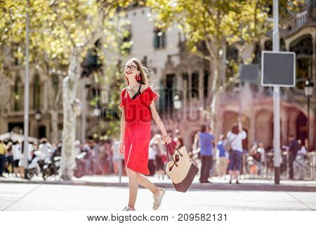 Lifestyle portrait of a beautiful woman in red dress crossing the central city avenue in Barcelona