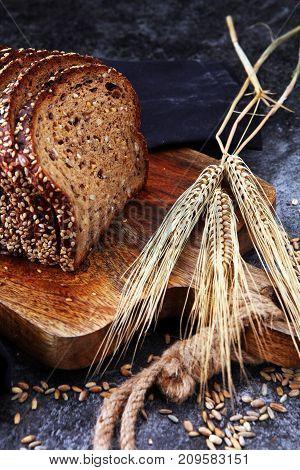 Sliced rye bread on cutting board. Whole grain rye bread with seeds