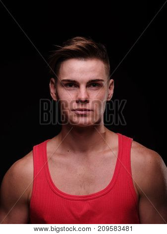 Close-up portrait of a gorgeous, thoughtful, confident young man with stylish haircut, wearing a red sporty t-shirt on a black background.