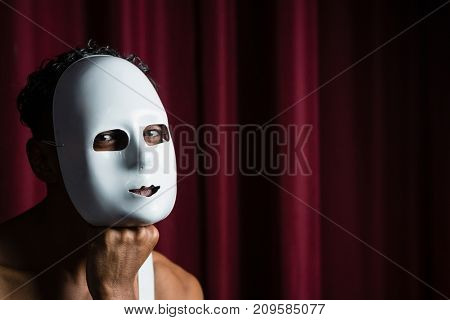Portrait of artist wearing white mask on his face in stage