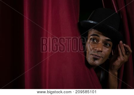 Close-up of ballet dancer peeking through a stage curtain