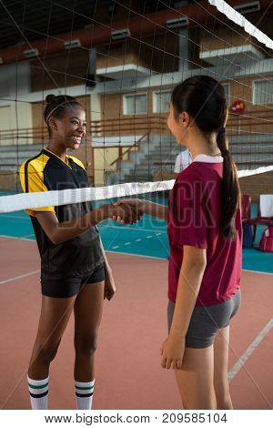 Two female players shaking hands with each other in the volleyball court