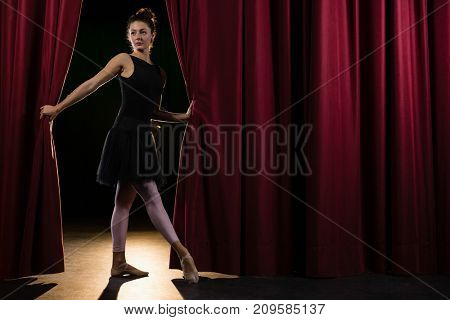 Beautiful ballerina posing in front of massive red stage curtain