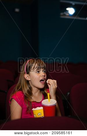 Girl having popcorns and drink while watching movie in theater
