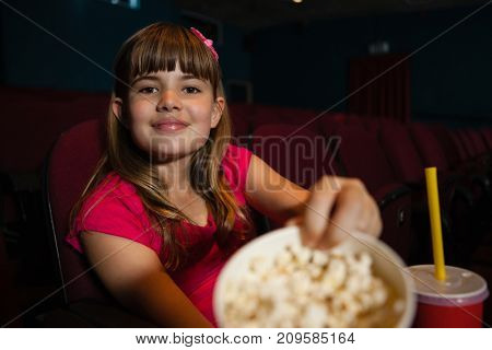 Portrait of girl showing popcorn container while sitting in movie theater