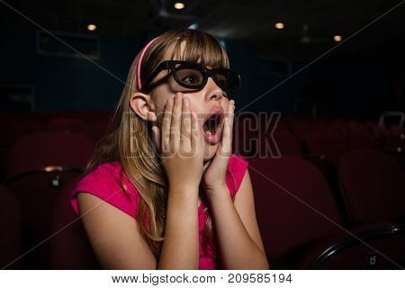 Surprised girl wearing 3D glasses while watching movie in theater