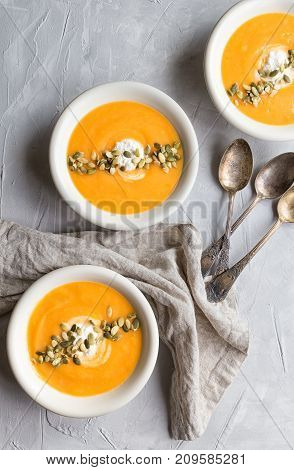 Fresh homemade pumpkin soup with ricotta cheese and seeds on gray concrete background. Top view.