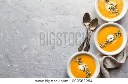 Fresh homemade pumpkin soup with ricotta cheese and seeds on gray concrete background. Top view. Copy space area.