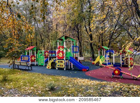 Empty children's playground in a park in autumn. Children are adult. Children are at school. The concept of city improvement taking care of children walking outdoors in any weather. Place for the inscription
