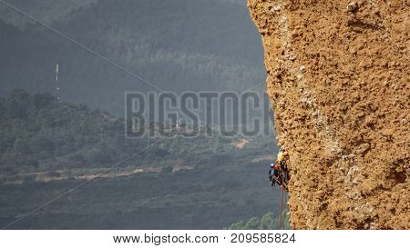 Long shot of group of male climbers hanging by a cliff against countryside