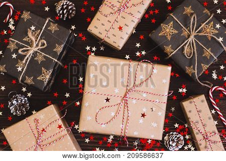 Christmas holiday gift box on decorated festive table with pine cones and sparkle stars on wooden background. Packaging gift wrap and ribbons twine. Winter time new year poster