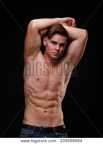Portrait of a passionate, strong, masculine young man with a perfect torso and muscular arms, posing shirtless on a black background.
