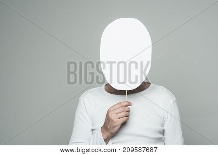 Man With Paper Nameplate Hiding Face On Grey Background