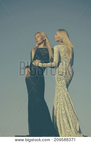 Opposites and contrasts concept. Women wearing black and white dresses. Fashion and beauty. Choice decision and future. Two girls with long blond hair posing on grey sky.