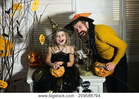 Father And Daughter With Halloween Decor. Wizard And Little Witch