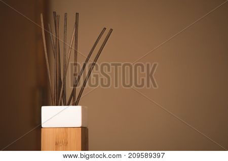 Simple portrait of incense sticks in a plain background